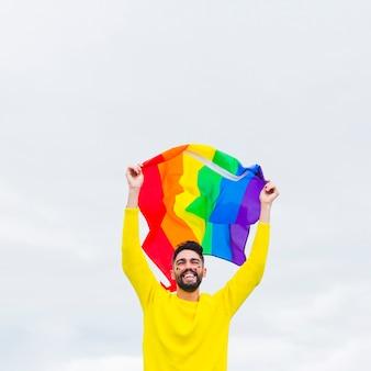Homosexual de pie y sosteniendo la bandera lgbt sobre la cabeza