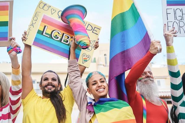 Los homosexuales se divierten en el desfile del orgullo gay con banderas y pancartas lgbt al aire libre: enfoque principal en la cara superior