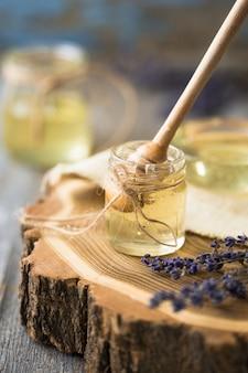 Honey pot, cazo, tarro de miel fresca, panal en una mesa de madera al aire libre. miel con cucharón de miel en mesa de madera