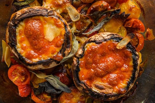 Hongos portobello, horneados con queso cheddar, tomates cherry y salvia en una olla de vidrio en la vista superior de fondo oscuro de metal rústico antiguo de cerca.