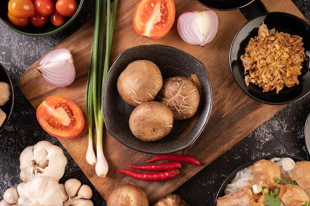 Hongos shiitake con ajo, tomate, pimiento, cebolleta y cebolla roja sobre un piso de cemento negro.