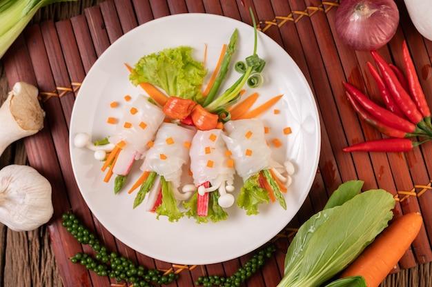 Hongos, zanahorias, espárragos y lechuga atados con fideos