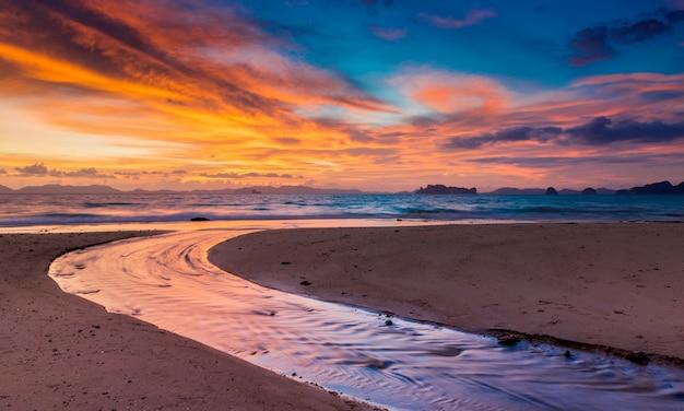 Hora del atardecer en la playa con paisaje crepuscular.