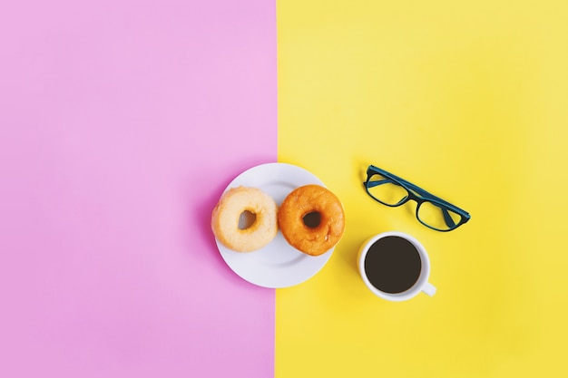 Hora del café, café negro y donuts, anteojos en fondo pastel