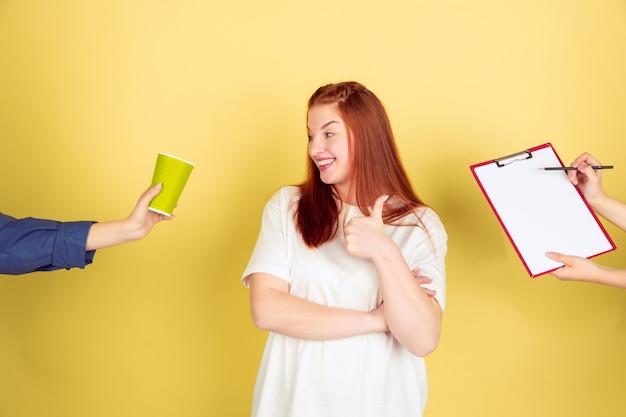 Hora de cafe. retrato de mujer joven caucásica sobre fondo amarillo de estudio, demasiadas tareas. cómo administrar el tiempo correctamente. concepto de trabajo de oficina, negocios, finanzas, autónomo, autogestión, planificación.