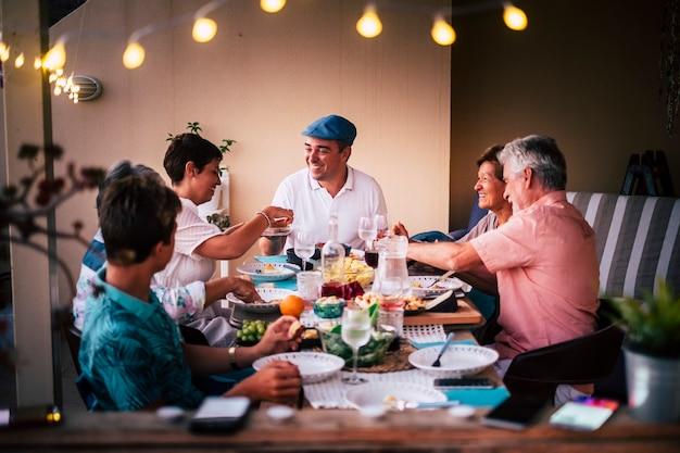 Hora de la cena en amistad con personas de diferentes edades todos juntos divirtiéndose y disfrutando de la noche con sonrisas y felicidad.