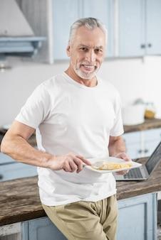 Hora de la cena. persona del sexo masculino atractivo que expresa positividad mientras come tortilla y mirando directamente a la cámara