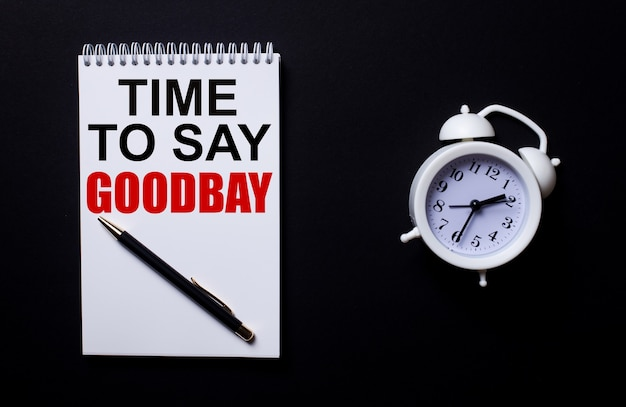 La hora de decir adiós está escrito en un bloc de notas blanco cerca de un despertador blanco en una pared negra.