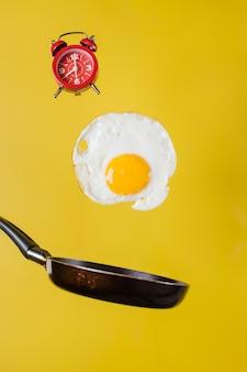 Hora del desayuno. un huevo frito y una sartén con un reloj levitan en el aire