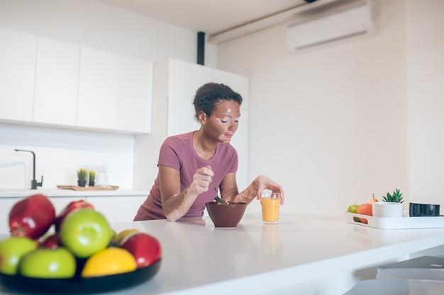 Hora del desayuno. linda joven de piel oscura con un desayuno saludable