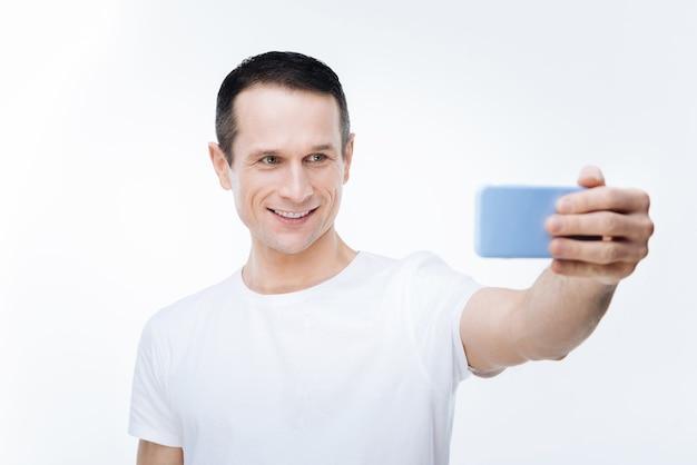 Hora de hacerse un selfie. feliz hombre encantado positivo sonriendo y tomando selfie mientras está de buen humor