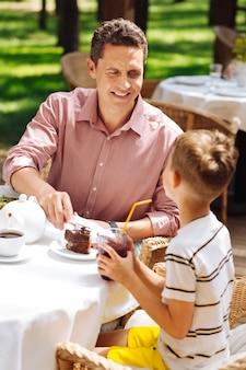 Hora del postre. padre vistiendo elegante camisa rosa comiendo sabroso postre dulce con su pequeño y lindo hijo