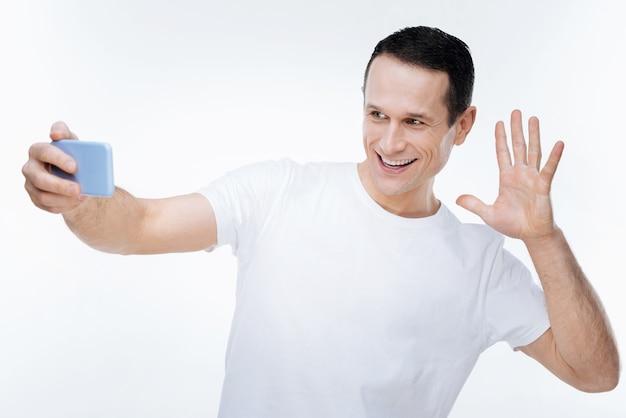 Hora de las selfies. hombre agradable alegre feliz sonriendo y mostrando su mano mientras toma selfie con su teléfono inteligente