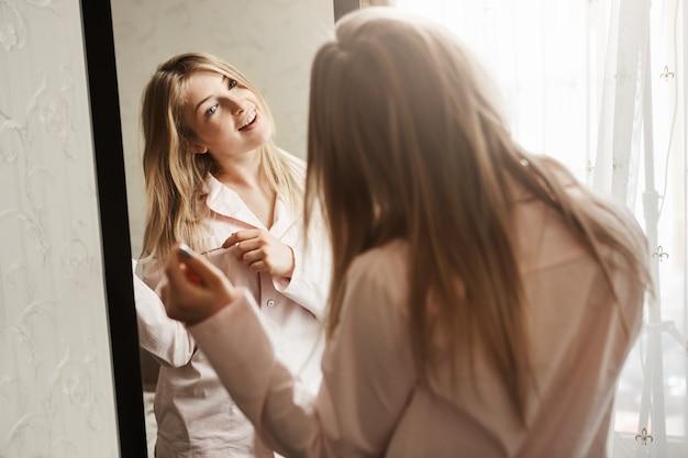 Hora de vestirse y fue a conocer aventuras. toma casera de la hermosa rubia caucásica mirando en el espejo, vistiendo ropa de dormir y tocando el mechón de cabello, pensando en un nuevo peinado