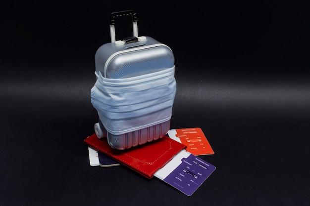 Hora de viajar. concepto de cancelación de vuelo y descanso seguro durante una pandemia de coronavirus covid-19. maleta para viajar con mascarilla médica y billetes de avión con pasaporte.