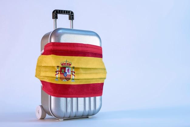 Hora de viajar. el concepto de descanso seguro durante una pandemia de coronavirus covid-19. maleta de viaje con antifaz médico y bandera española.