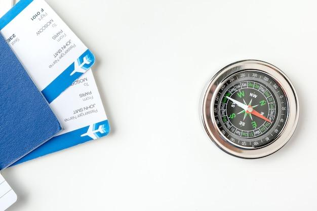 Hora de viajar. idea para el turismo con billetes de avión y brújula en blanco