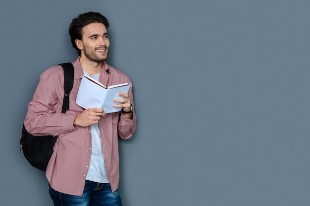 Hora de viajar. turista masculino guapo alegre sonriendo y leyendo un guía turístico mientras planifica su viaje
