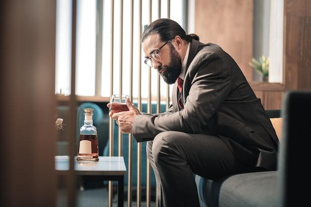 Hora del whisky. economista experimentado maduro que se siente preocupado mientras está sentado en el vestíbulo del hotel y bebe whisky