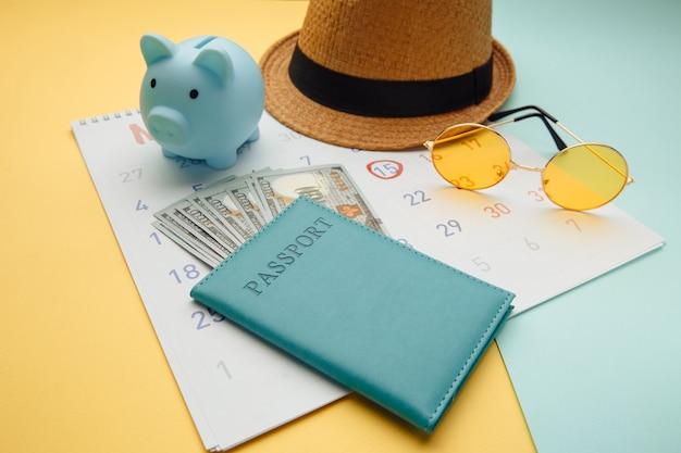 Horario de calendario de verano con pasaporte, gafas de sol y alcancía en superficie azul amarillo. viajes, turismo, concepto de vacaciones