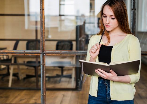 Horario de organización de la mujer hermosa joven en oficina