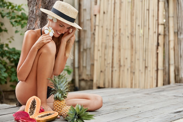 Horario de verano, estilo de vida saludable, nutrición y concepto de comida. feliz mujer encantadora con sombrero de paja, rodeada de frutas exóticas maduras, va a hacer ensalada, le gusta la piña dulce, la papaya y la fruta del dragón