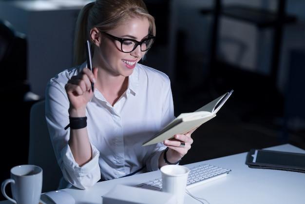 Horas de trabajo agradables. secretaria atractiva alegre sonriente sentada en la oficina y tomando notas mientras expresa positividad