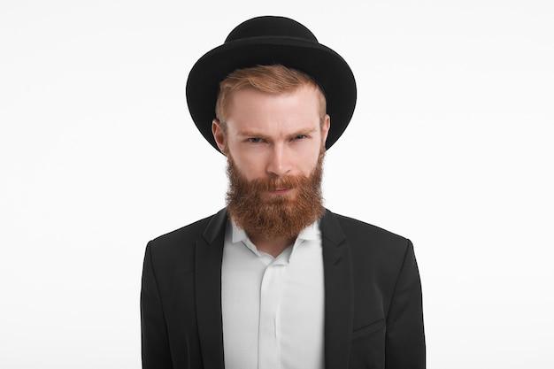 Horizontal guapo elegante joven pelirrojo masculino con barba difusa, frunciendo los ojos y frunciendo los labios, con mirada sospechosa. hombre sin afeitar con sombrero y traje disgustado y enojado