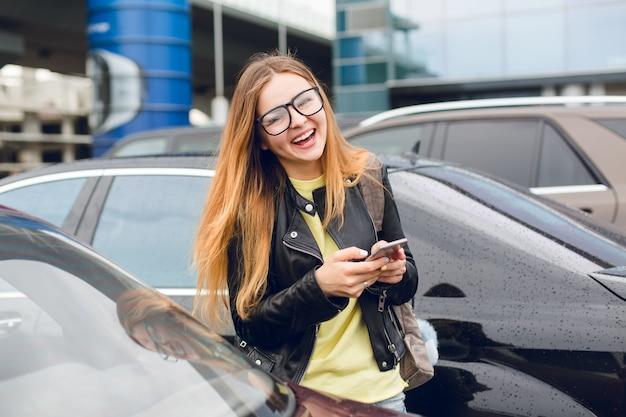 Horizontal retrato de niña con cabello largo con gafas caminando en la zona de estacionamiento. viste suéter amarillo y chaqueta negra. ella está sonriendo a la cámara y sostiene el teléfono en las manos.