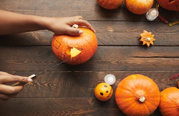 Horizontal vista desde arriba foto de manos tallando calabaza madura para la fiesta de santificación con cuchillo de cocina en la mesa de madera de color marrón oscuro