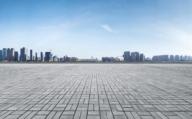 Horizonte panorámico y edificios con piso cuadrado de concreto vacío, ciudad nueva de qianjiang