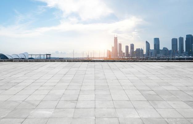 Horizonte panorámico y edificios con piso cuadrado de hormigón vacío, qingdao, china