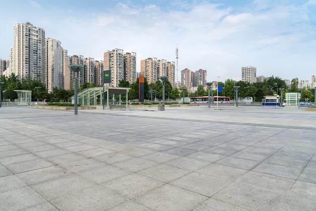 Horizonte panorámico y edificios con piso cuadrado de hormigón vacío