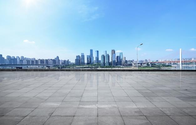 Horizonte panorámico y edificios con suelo cuadrado concreto vacío
