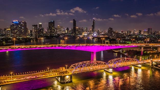 Horizonte y rascacielos de la ciudad de bangkok de la visión aérea en la noche con el edificio del negocio en el centro de la ciudad de bangkok, chao phraya river, bangkok, tailandia.