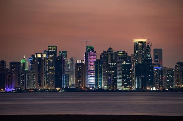 Horizonte vibrante de doha en la noche como se ve desde el lado opuesto de la puesta de sol de la bahía de la ciudad capital.