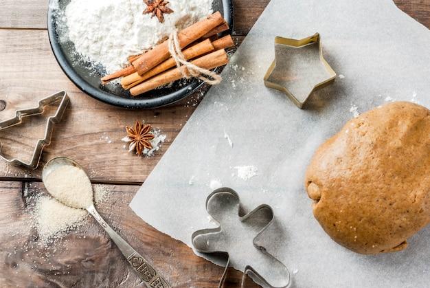 Horneado navideño masa de jengibre para pan de jengibre hombres de pan de jengibre estrellas árboles de navidad rodillo especias (canela y anís) harina en la cocina de la casa mesa de madera