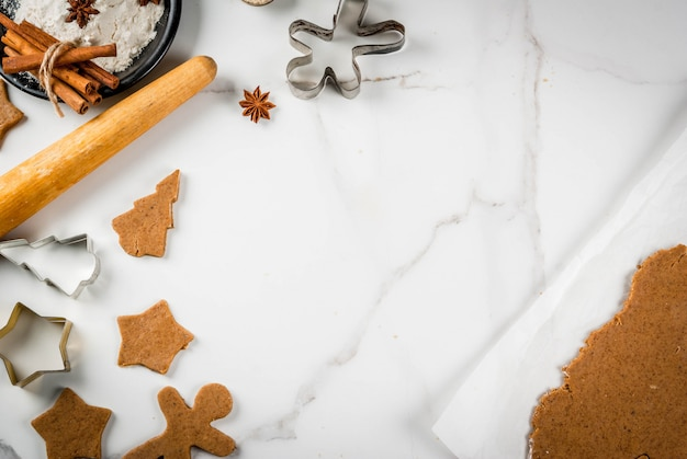 Horneado navideño masa de jengibre para pan de jengibre hombres de pan de jengibre estrellas árboles de navidad rodillo especias (canela y anís) harina en la cocina de la casa mesa de mármol blanco