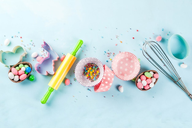 Hornear dulce para pascua, cocinar con hornear: con un rodillo, batir para batir, cortadores de galletas, espolvorear azúcar, harina. fondo azul claro, vista superior copyspace