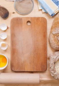 Hornear fondo cálido claro con tabla de cortar, cáscara de huevo, pan, harina, rodillo. ingredientes para la repostería.