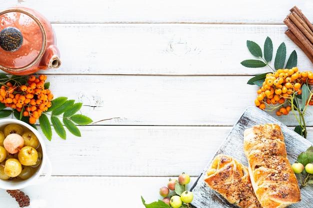 Hornear con manzana, manzana recién horneada y rollos de canela hechos de hojaldre sobre una mesa de madera blanca. vista superior, estilo rústico, espacio de copia.