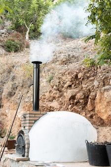 Horno artesanal de leña empotrado en el exterior echando humo por la chimenea