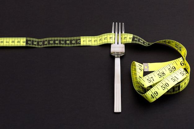 Horquilla con una cinta métrica, dieta o concepto de alimentación saludable.