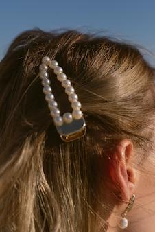 Horquilla de perlas en el cabello de una chica rubia