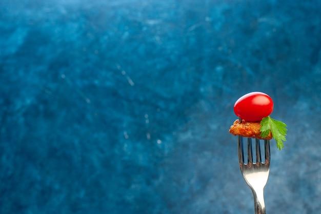 Horquilla con tomate y pollo sobre fondo azul.