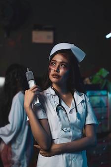 Horror aterrador malvado médico de enfermería loco sostuvo el cuchillo, mujer zombie gosth con concepto de halloween
