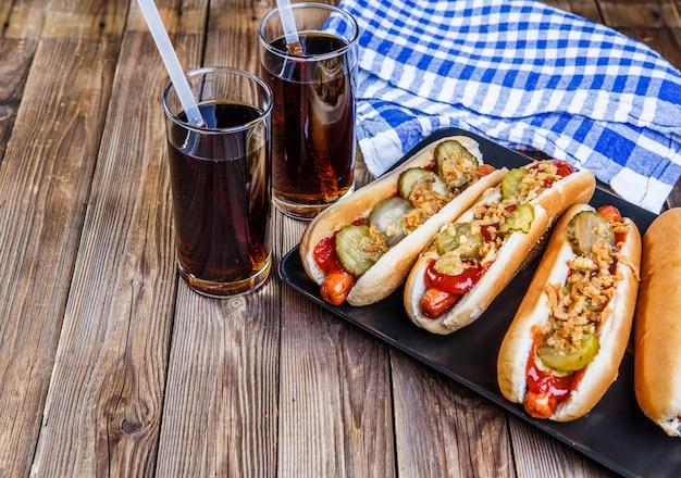 Hot dog americano con pepinillos, cebollas, ketchup, mostaza y dos refrescos.