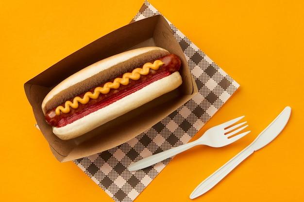 Hot dog clásico con salsa de tomate salchicha y mostaza sobre fondo naranja menú de restaurante entrega tacke ...