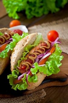 Hot dog con ketchup mostaza y lechuga en mesa de madera