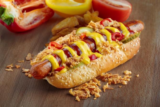 Hot dog con mostaza amarilla y salsa de tomate en tablero de madera